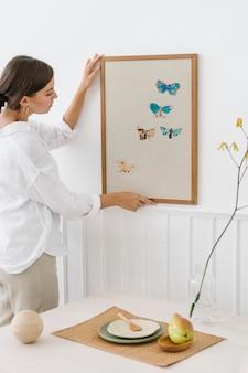 Femme accrochant un cadre photo sur un mur blanc