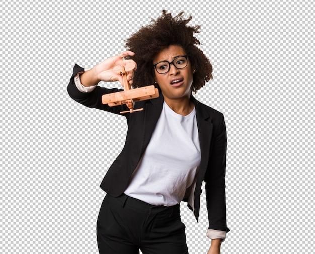 Femme d'affaires noire jouant avec un avion en bois