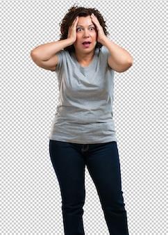 Femme d'âge moyen frustrée et désespérée, en colère et triste avec les mains sur la tête