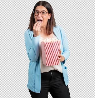 Femme d'âge moyen heureuse et fascinée, tenant un seau de pop-corn rayé