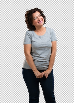 Femme d'âge moyen levant les yeux, pensant à quelque chose d'amusant et ayant une idée, concept d'imagination, heureux et excité