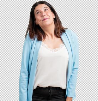 Femme d'âge moyen levant les yeux, pensant à quelque chose d'amusant et ayant une idée