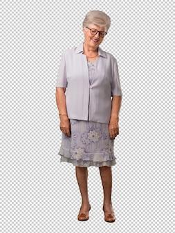 Femme âgée au corps entier qui croise les doigts, souhaite avoir de la chance pour ses projets futurs