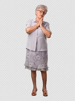 Femme âgée au corps entier se rongeant les ongles, nerveuse et très angoissée et inquiète pour l'avenir, en proie à la panique et au stress