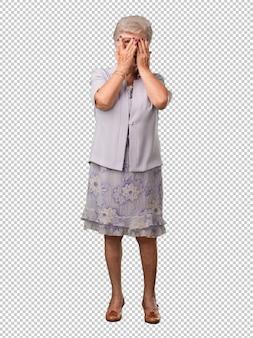 Femme âgée au corps entier se sent inquiet et effrayé, regardant et couvrant le visage, concept de peur et d'anxiété