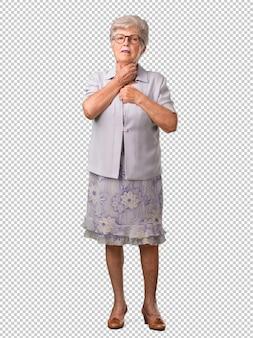 Femme âgée au corps entier souffrant de maux de gorge, malade à cause d'un virus, fatiguée et dépassée