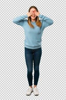 Femme blonde avec une chemise bleue couvrant les yeux par des mains. surpris de voir ce qui nous attend