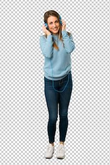 Femme blonde avec une chemise bleue, écouter de la musique avec des écouteurs