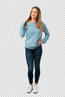 Femme blonde avec une chemise bleue avec une expression fatiguée et malade