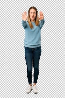 Femme blonde avec une chemise bleue faisant un geste d'arrêt pour déçu par un avis