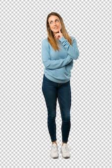 Femme blonde avec une chemise bleue pense à une idée tout en levant les yeux