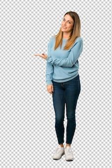 Femme blonde avec une chemise bleue présentant une idée tout en regardant en souriant