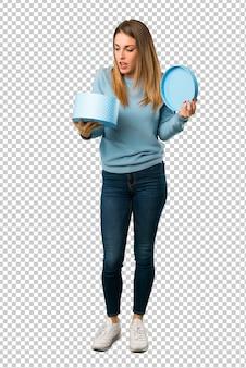 Femme blonde avec une chemise bleue tenant une boîte cadeau en mains