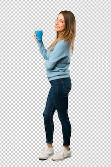 Femme blonde avec une chemise bleue tenant une bonne tasse de café