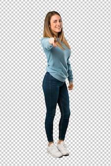 Une femme blonde avec une chemise bleue vous montre du doigt avec une expression confiante