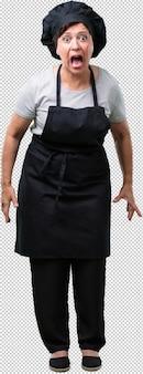 Femme de boulanger d'âge moyen plein de corps hurlant de colère, expression de folie et d'instabilité mentale, bouche ouverte et yeux mi-ouverts, concept de folie