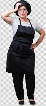 Femme de boulanger d'âge mûr complet du corps inquiet et accablé, oublieux, réaliser quelque chose, expression de choc d'avoir commis une erreur