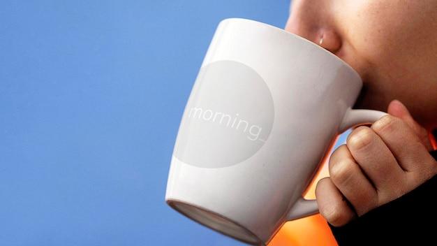 Femme buvant une boisson chaude dans une maquette de tasse