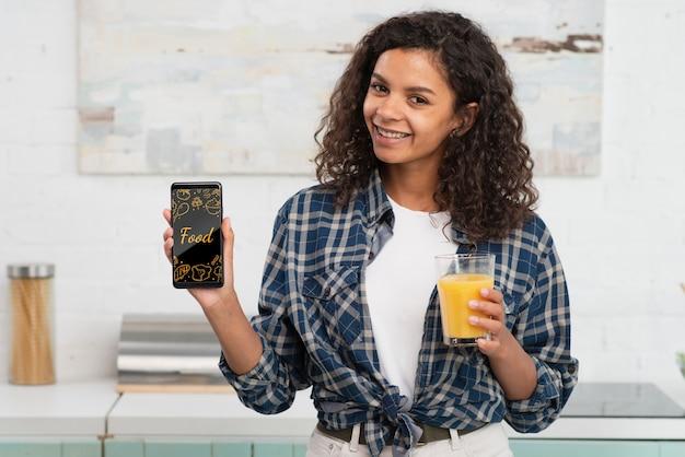 Femme buvant du jus de fruits frais à la maison