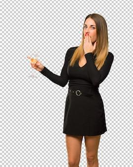 Femme avec champagne célébrant le nouvel an 2019, pointant le doigt sur le côté avec un visage surpris
