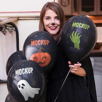 Femme en costume d'halloween tenant des ballons de maquette