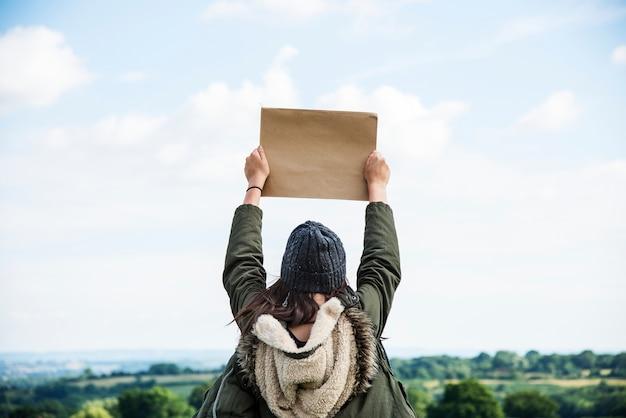 Femme dans la nature tenant le carton