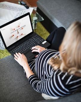 Femme enceinte sur le canapé à l'aide d'ordinateur