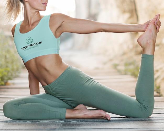 Femme faisant du yoga tout en portant un soutien-gorge de sport maquette