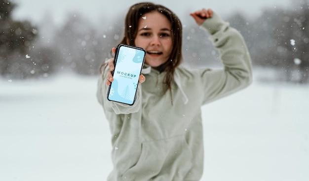 Femme heureuse sautant avec le téléphone