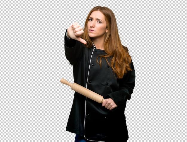 Femme jeune chef rousse montrant le pouce vers le bas de signe avec une expression négative