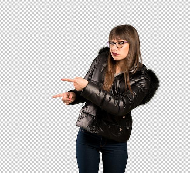 Femme à lunettes effrayée et pointant sur le côté