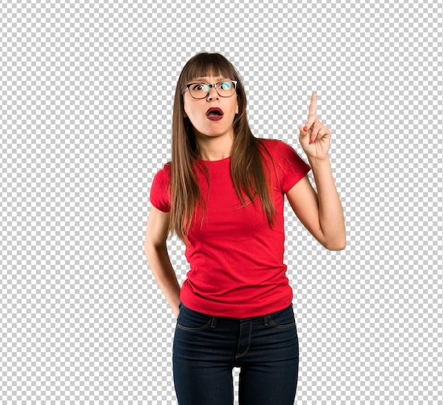 Femme à lunettes pointant vers le haut et surprise