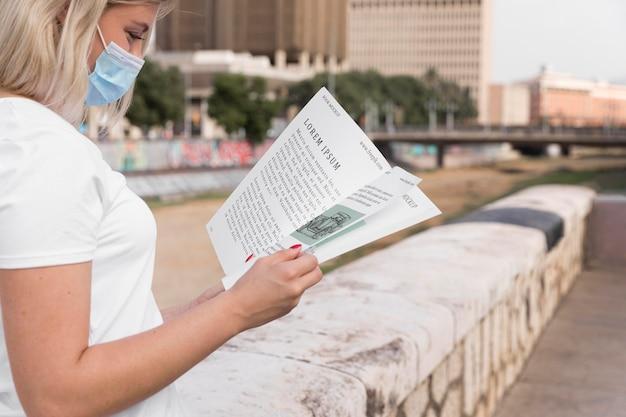 Femme, à, masque, livre lecture, sur, rue