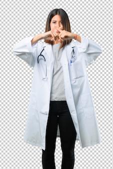 Femme médecin avec stéthoscope montrant un signe de fermeture bouche et geste de silence