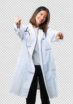 Femme médecin avec stéthoscope pointe le doigt sur vous en souriant