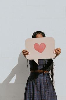 Femme montrant une bulle de dialogue avec une icône de coeur rose