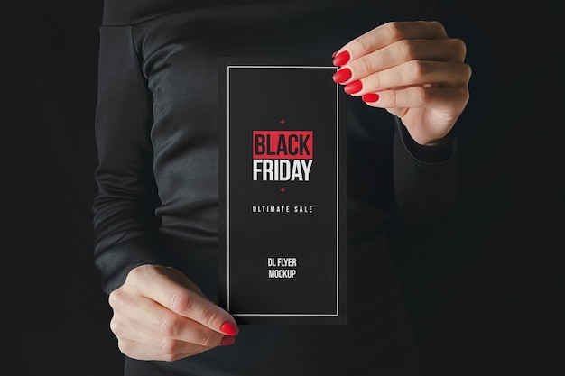 Femme en noir tenant une maquette de flyer dl