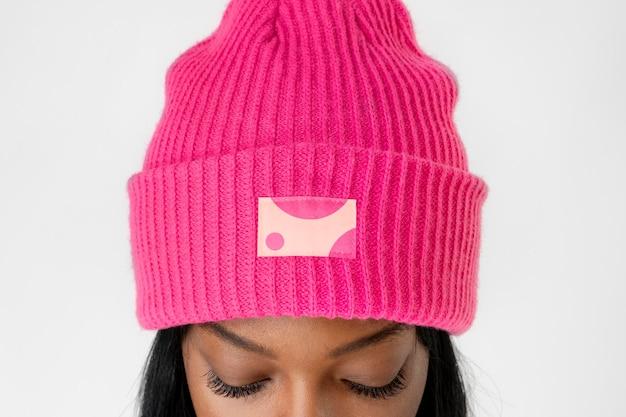 Femme noire portant une maquette de bonnet rose vif