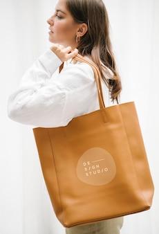 Femme portant une maquette de sac à main marron