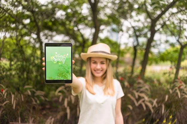 Femme présentant une maquette de tablette dans la nature
