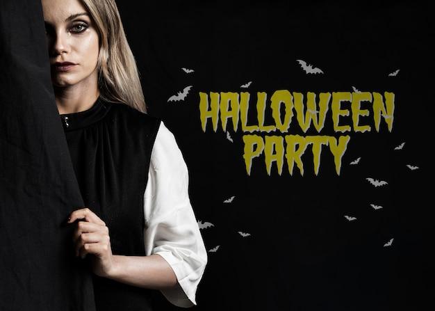 Femme se cachant derrière une photo d'halloween en tissu