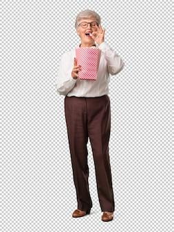 Femme senior pleine de corps, heureuse et fascinée, tenant un seau de maïs soufflé rayé,