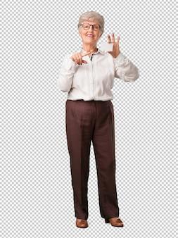 Femme senior pleine de corps souriant, confiant, offrant une carte de visite, a une entreprise florissante, copie espace pour écrire ce que vous voulez