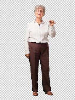 Femme senior pleine de corps souriant, confiant, offrant une carte de visite, a une entreprise prospère