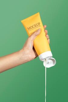 Femme serrant la crème d'une maquette psd de tube jaune