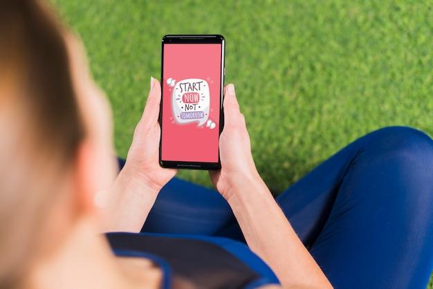 Femme sportive à l'aide de la maquette de smartphone