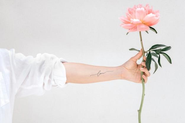 Femme avec un tatouage au bras tenant une pivoine le faon