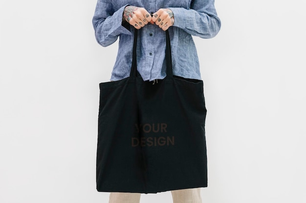 Femme tatouée dans une chemise en lin bleue tenant une maquette de sac fourre-tout noir
