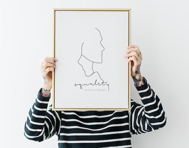Femme tatouée tenant une maquette de cadre photo
