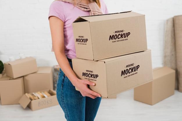 Femme tenant deux maquettes de boîtes de déménagement